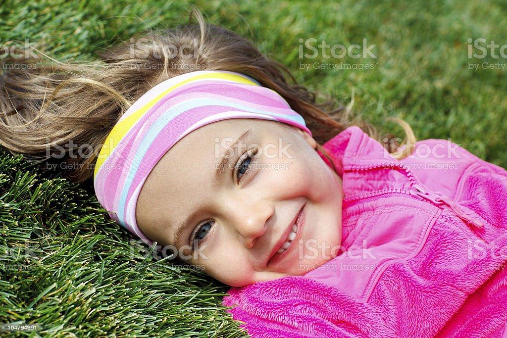 Preschool girl on green grass royalty-free stock photo