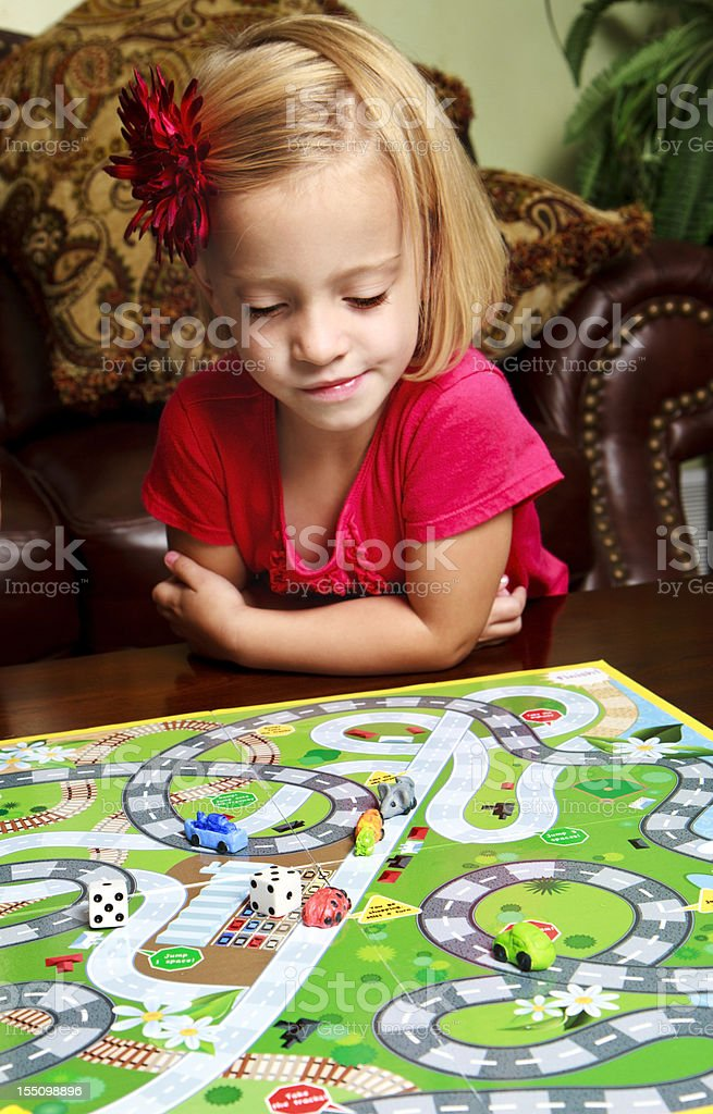Preschool Girl Playing A Board Game stock photo