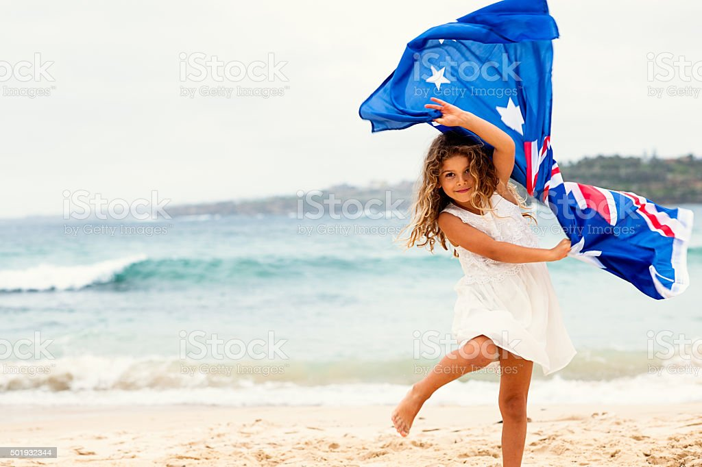 Preschool girl with Australian flag on the beach stock photo
