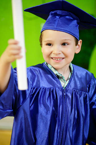 Happy kid and cute child on kindergarten graduated dress on gray white background