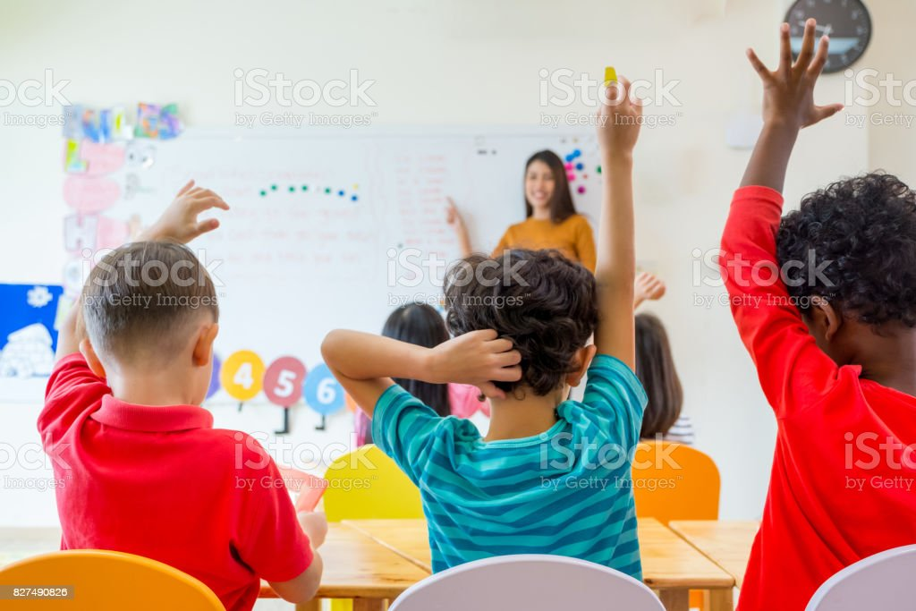 Preschool kid raise arm up to answer teacher question on whiteboard in classroom,Kindergarten education concept stock photo