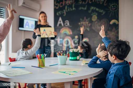 Preschool kids sitting in preschool/private school and learning letters with teacher