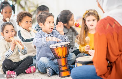 Multi-ethnic group of preschool children learning through the use of musical instruments