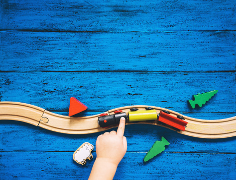 Preschool or kindergarten background with toys. Child's hands playing with wooden toy train set and railway on blue table. Kids dream, travel concept. Top view, flat lay, copy space.