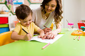 Little boy and teacher are studying in classroom