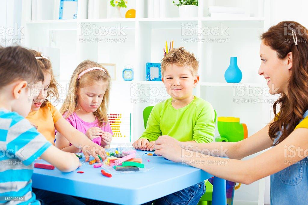 Group of preschool children having craft activities with color playdo...