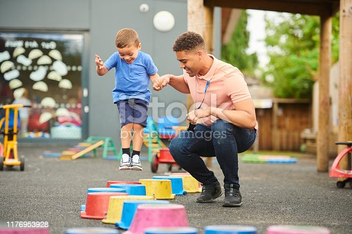 nursery worker with child in playground