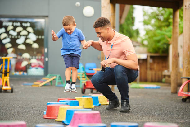 pre-school stepping stones nursery worker with child in playground preschool age stock pictures, royalty-free photos & images