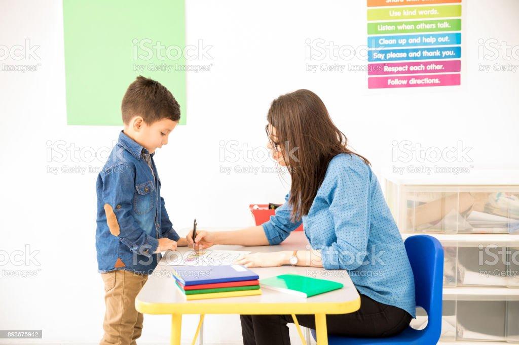 Preschool student getting her work graded stock photo