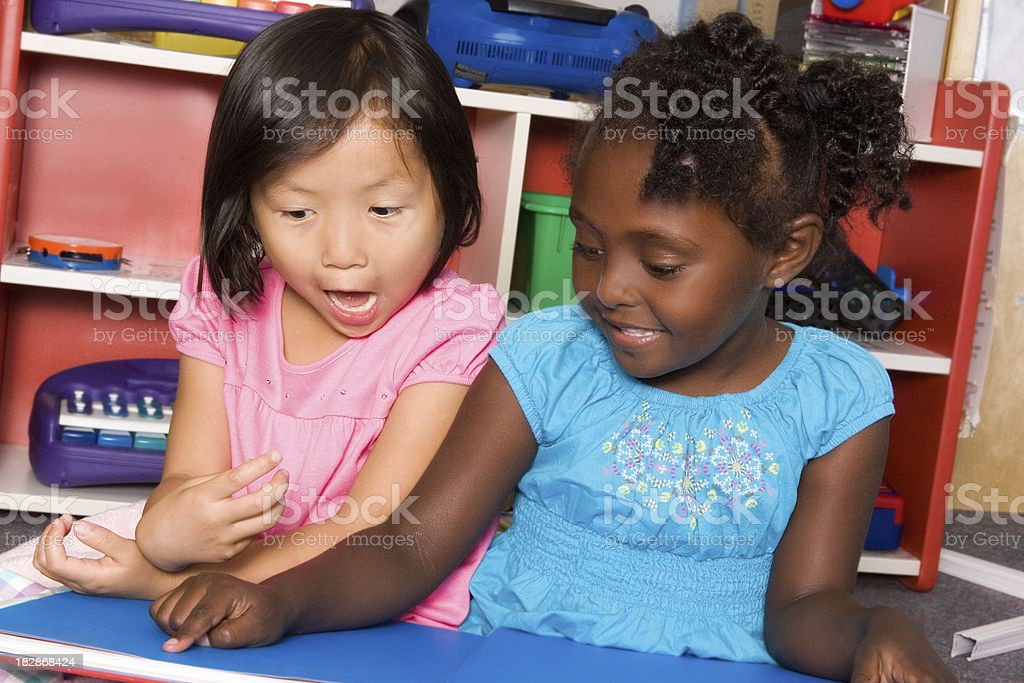 Preschool surprised at what she is shown in book royalty-free stock photo