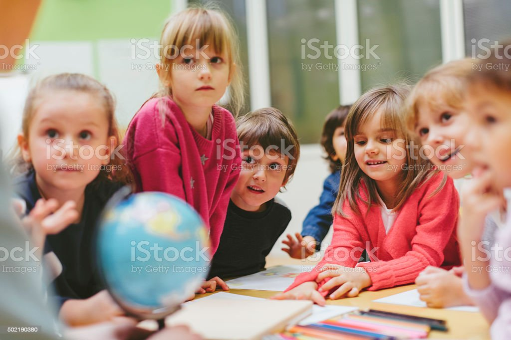Preschool teacher and children learning in classroom. Preschool teacher teaching her children about geography. Using globe and asking the questions. Children listening and answering. Models in this shot are part of real kindergarten group and their teacher. Shot with Canon EOS 5Ds. 2015 Stock Photo