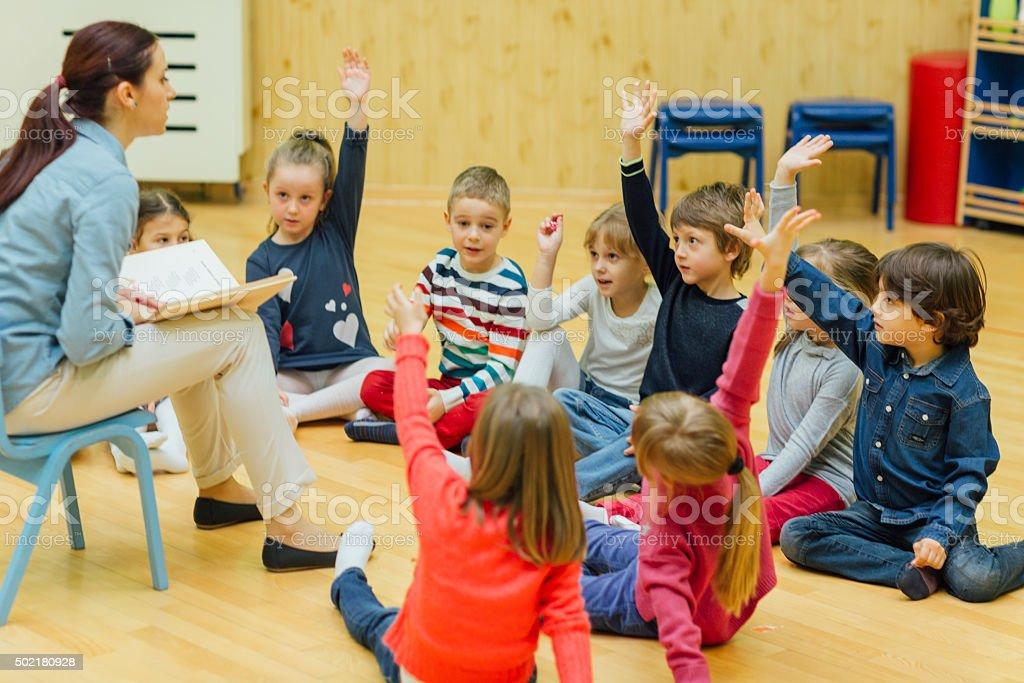Enseignants et enfants d'âge préscolaire avec des mains surélevées en salle de classe. - Photo