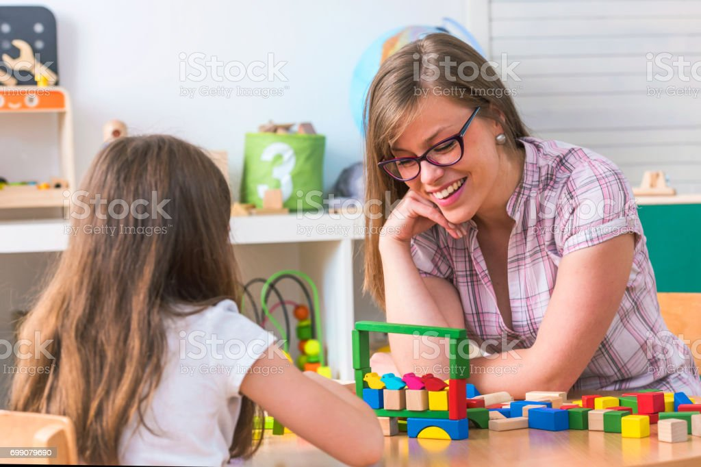 Preschool Teacher and Cute Girl Having Fun Time Playing stock photo