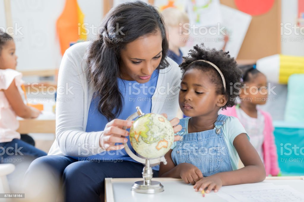 Preschool teacher and student look at globe stock photo