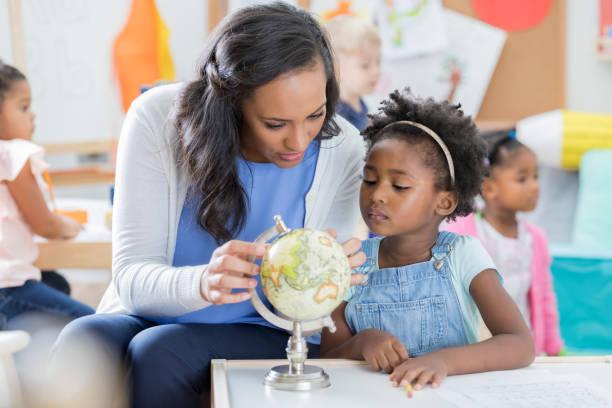 Ecolière et son institutrice préscolaire regardent globe - Photo