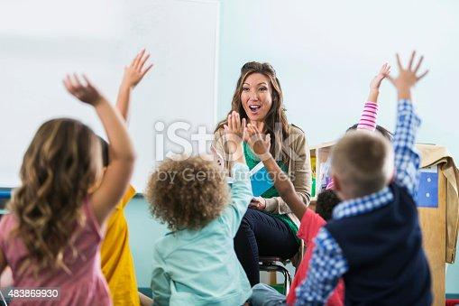 istock Preschool teacher, children raising hands in class 483869930