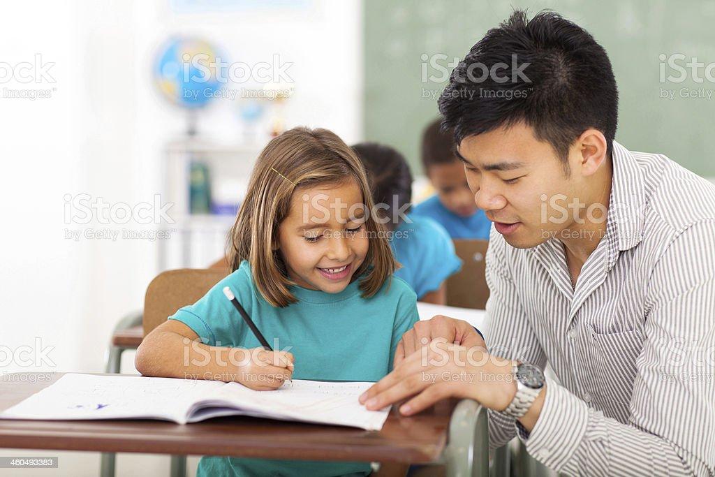preschool teacher helping little girl with class work stock photo