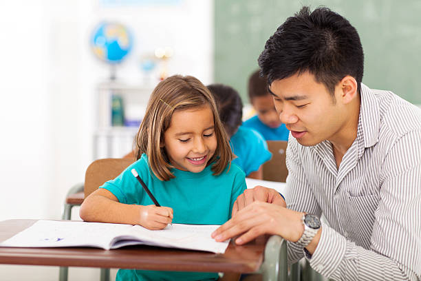 preschool teacher helping little girl with class work - elementary age stock photos and pictures