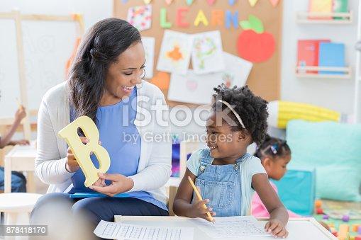 istock Preschool teacher helps student with alphabet 878418170