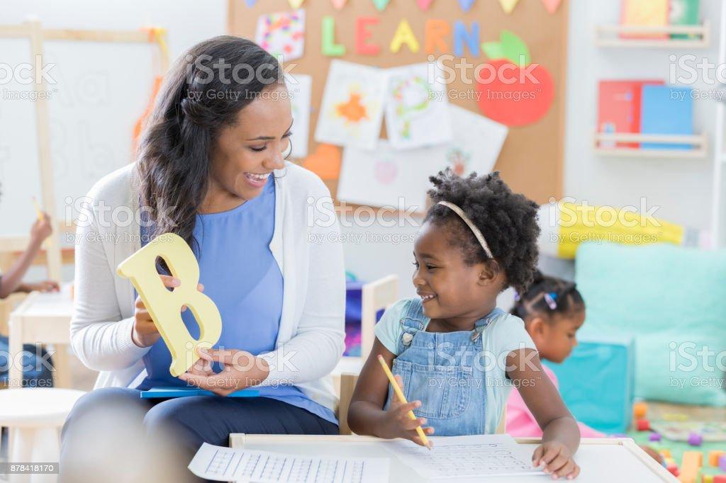 Preschool teacher helps student with alphabet stock photo