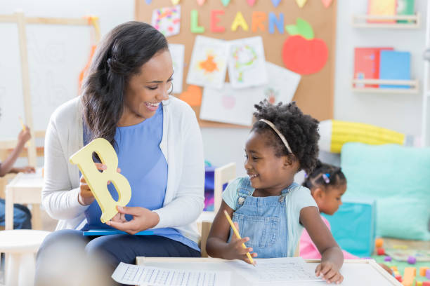 Preschool teacher helps student with alphabet Cheerful mid adult female preschool teacher holds a letter