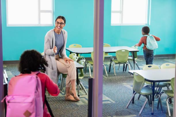maestra de preescolar en estudiante de aula saludo - regreso a clases fotografías e imágenes de stock