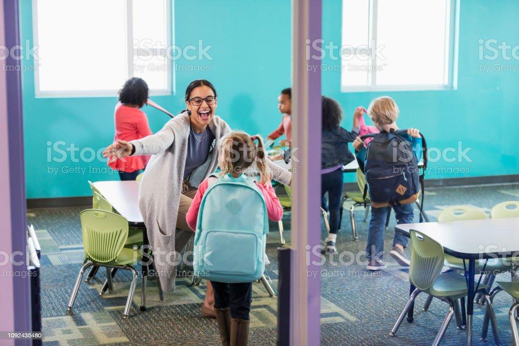 Maestra de preescolar en saludo estudiantes de aula - foto de stock