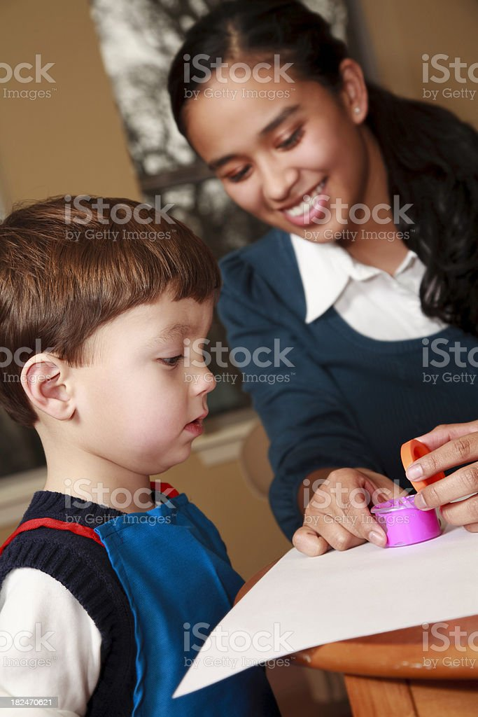 Preschool Teacher or Daycare Worker Helping Child with Finger Paint royalty-free stock photo