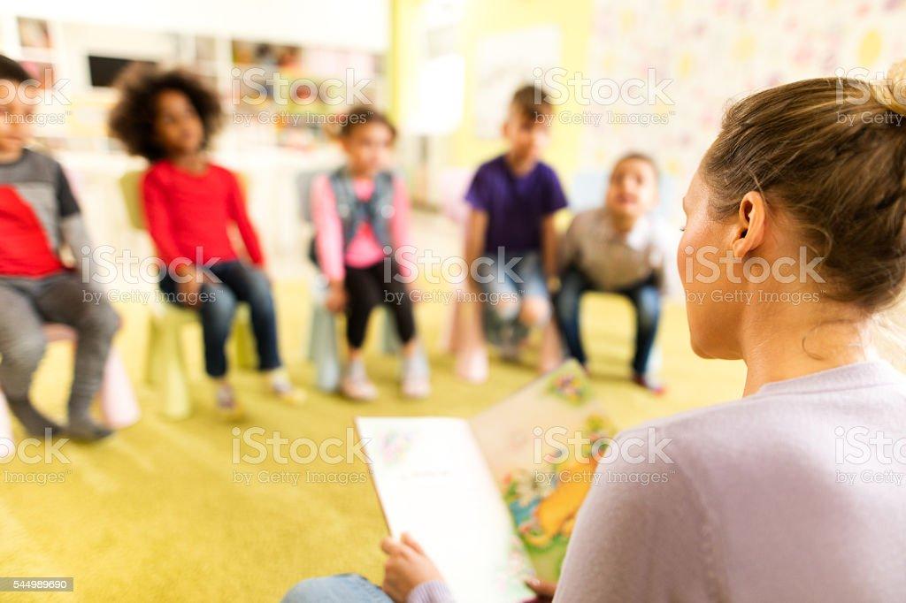 Preschool teacher reading a story to children at kindergarten. stock photo