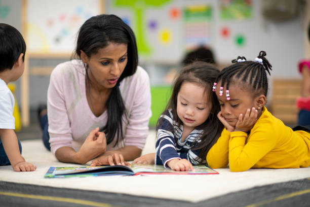 Preschool teacher reading with students stock photo