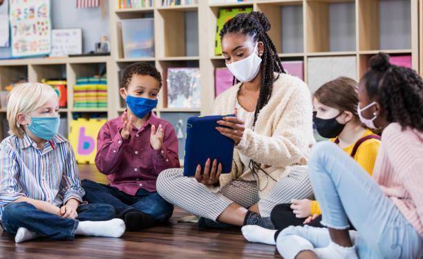 Preschool teacher, students in class, wearing masks stock photo