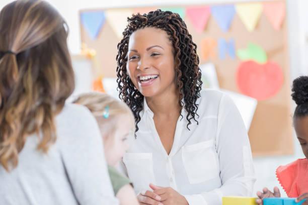 Preschool teacher talks with a student's mom stock photo