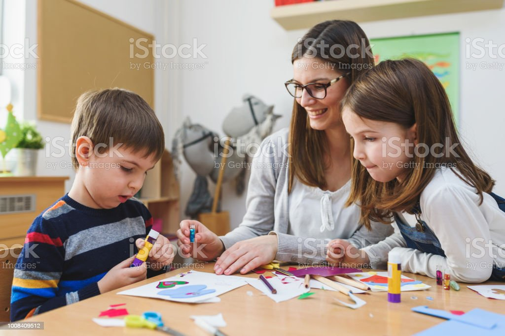Preschool Teacher With Children At Kindergarten Creative Art Class