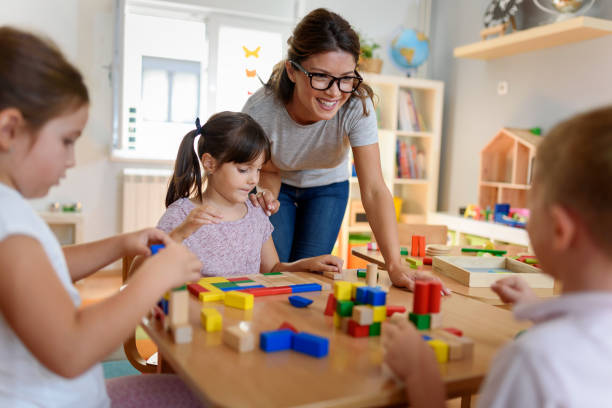 Preschool teacher with children playing with didactic toys Preschool teacher with children playing with colorful wooden didactic toys at kindergarten preschool age stock pictures, royalty-free photos & images