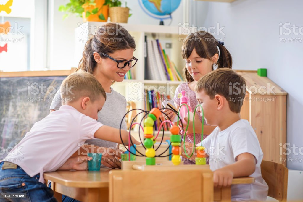 Preschool teacher with children playing with colorful wooden didactic...
