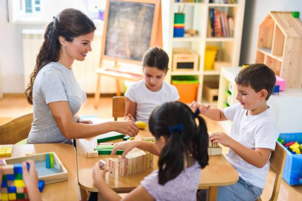kindergärtnerin mit kindern mit didaktischen spielzeugen spielen - erzieherin stock-fotos und bilder