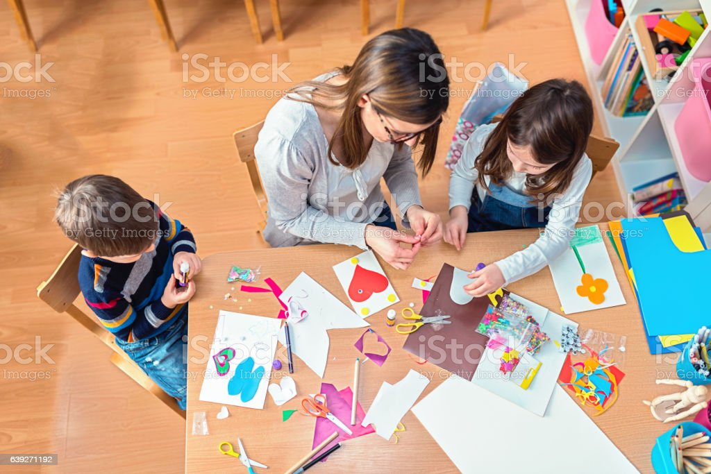 Preschool teacher with kids having creative activities stock photo