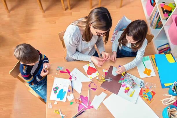 preschool teacher with kids having creative activities - tutore mestiere nel campo educativo foto e immagini stock
