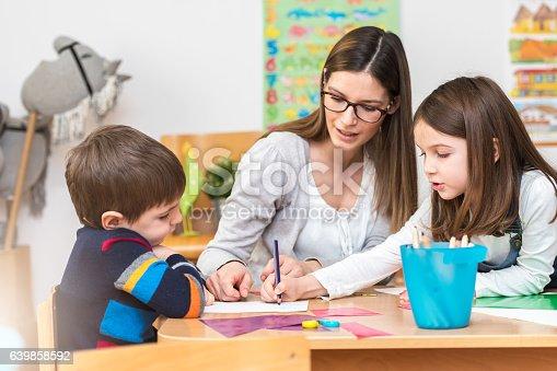 639271192istockphoto Preschool teacher with kids having creative activities 639858592