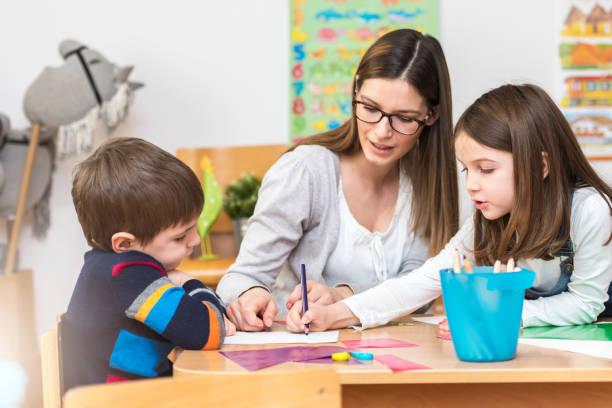 preschool teacher with kids having creative activities - erzieherin stock-fotos und bilder