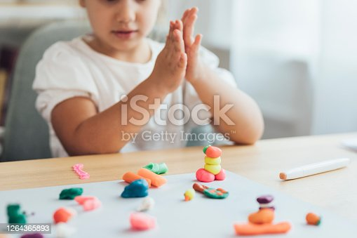 Creative kids: an anonymous little girl playing with plasticine at home.