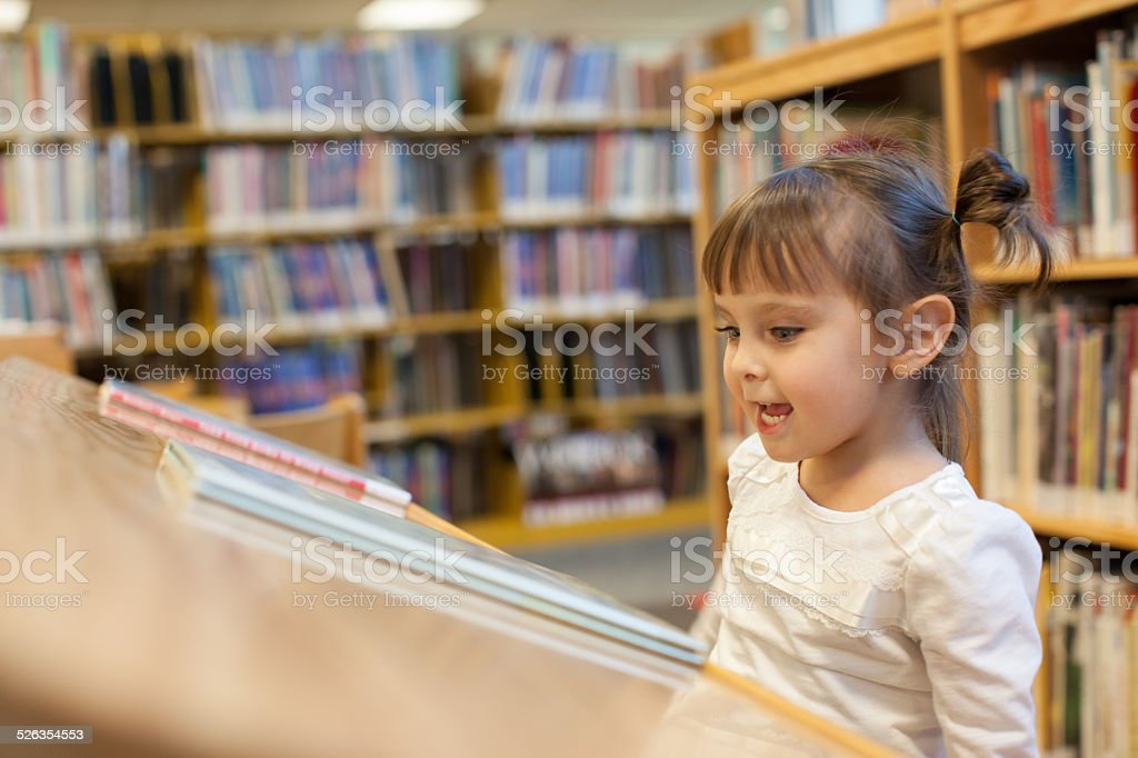 Preschooler Child is Reading a Book At the Library stock photo