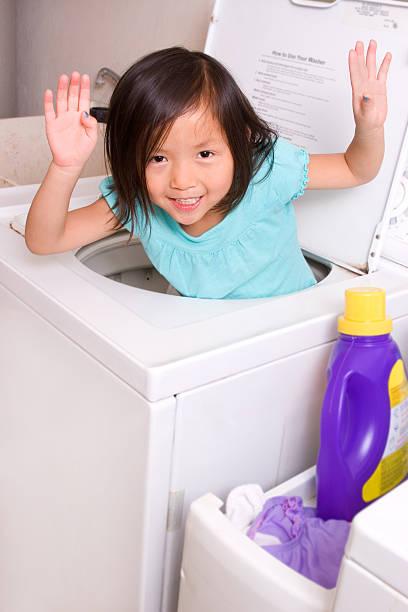 vorschulkind heraus. der waschmaschine - chinese wäscherei stock-fotos und bilder