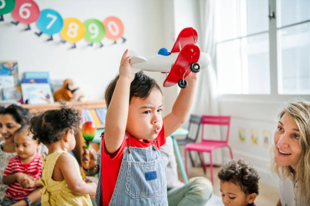 Preschooler enjoying playing with his airplane toy stock photo