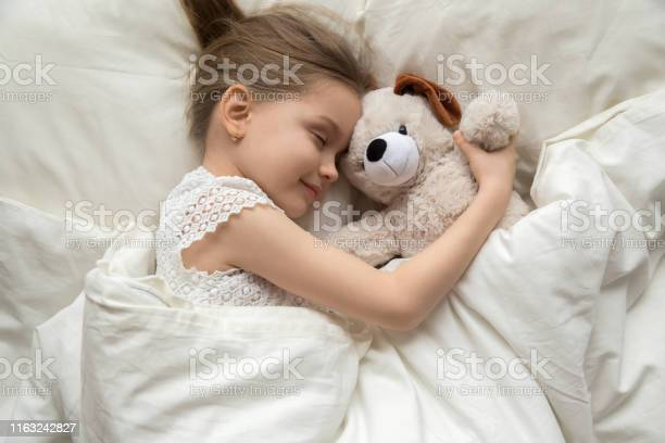 Preschooler girl hug teddy sleeping peacefully in cozy bed picture id1163242827?b=1&k=6&m=1163242827&s=612x612&h=d3dmamgsaopiduxkcy6ntkspz1v ejfz b150goe2jk=