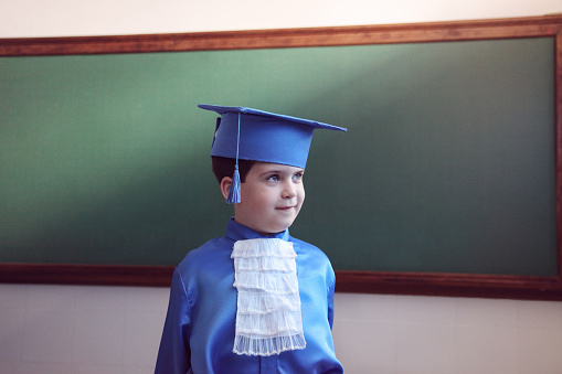 Boy with autism shows excitement as he holds onto his diploma now that he has graduated preschool and will advance to kindergarten.