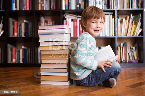 istock preschooler little boy reading a book in the library. the little boy with books near a bookcase 906233806