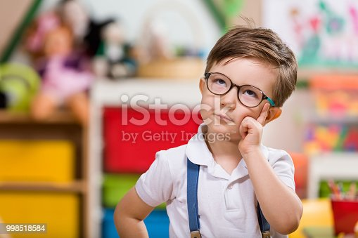 Little boy planning in classroom.