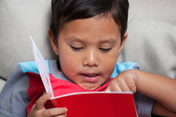 A preschooler pronouncing  simple phonics is reading from an early reader style story book. stock photo