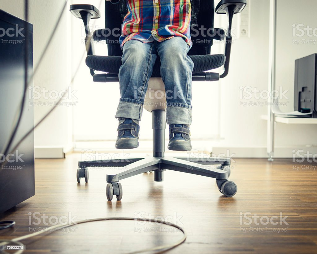 Preschooler Sitting at Grown-ups Office Desk, View of Feet stock photo